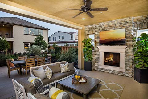Outdoor lounge area of a beautiful house designed and decorated in gray, white and a touch of yellow.
