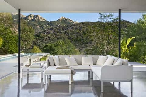A set of white, elegantly designed furniture in a building with a mountainous landscape behind it.