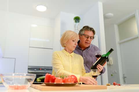 Adult male and female in the kitchen holding onto a glass of wine and staring keenly at a bottle of wine held by the woman.