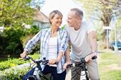 Elderly white couple riding bicycles in their neighborhood. They are both smiling and looking into each other's eyes.