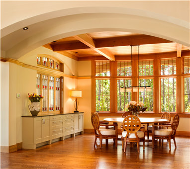 A traditional dining area with wooden floors, full of wooden furniture and other rich-colored items.