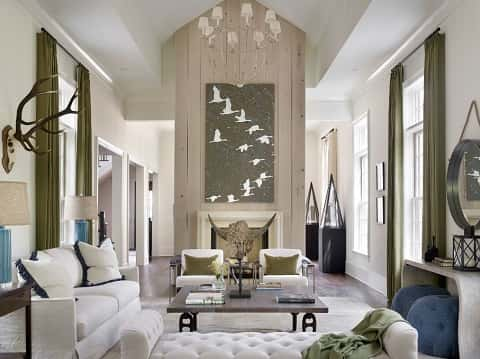 A rectangular shaped living room painted white and filled with white furniture and decor