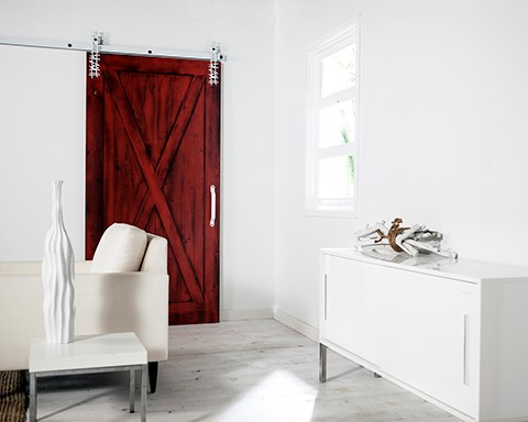 A section of a white room with a medium-sized red barn door.