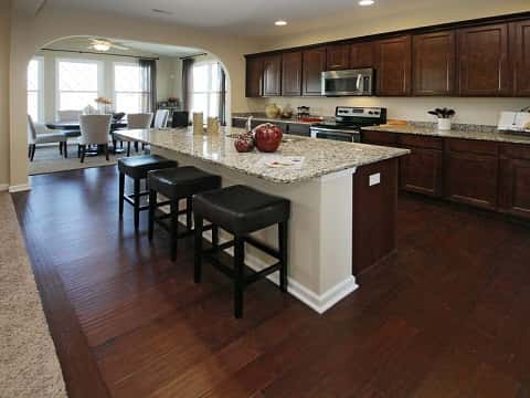 A large kitchen with tiled table, padded stools and polished wooden cabinets and floor adjacent a dining room.