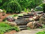 Stairs made of rock slabs and boulders to one end of the stairs is lined on both sides by flowers.