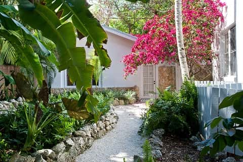 A courtyard narrowed to a walking path leading to the door of a building by colorful flowers and trees