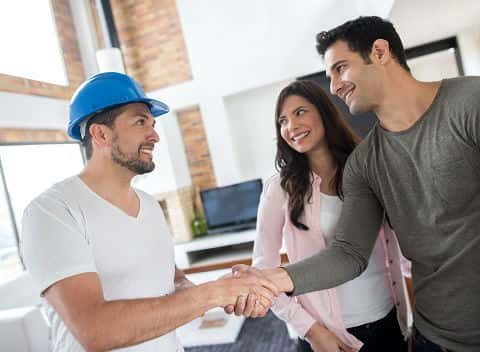 A young couple meeting a builder. The young man shaking hands with the builder.
