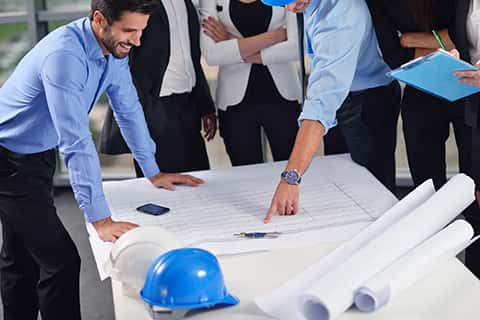 A group of business people analyzing building plans along with an engineer. The building plans are on the table along with a blue helmet