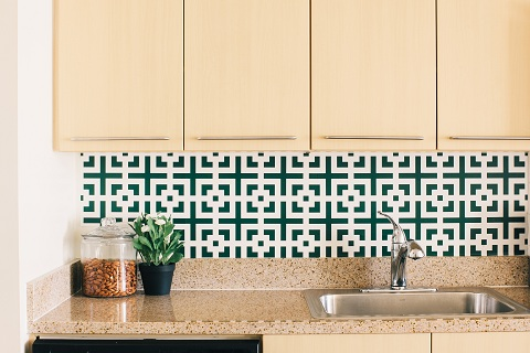 A kitchen sink with a tap. The wall is decorated with different designs of tiles.