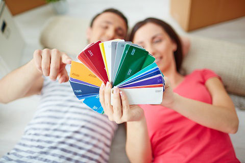 A couple in the process of designing their home look through different paint color options.