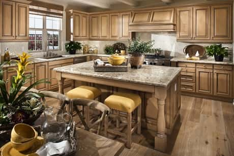 A kitchen area complete with wooden cabinets and chairs, plus tables, sinks and other items.