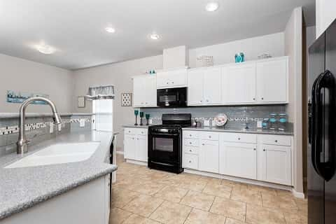 A beautiful kitchen with tiled floors. On the left is the sink, and further to the right is the kitchen cabinet.