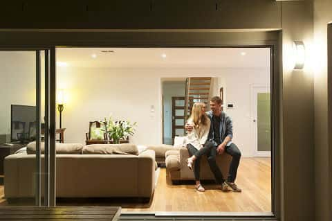 A couple happily shares a smile, seated inside a big house with an open-plan design.