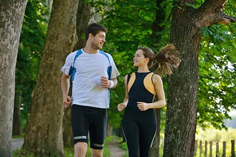 A young couple running and enjoying this activity. They wear sport equipment that suits to their activity.