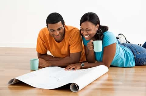 Couple inspecting floor plan while lying on the ground and smiling. The woman is holding her mug of coffee while the man has his own by his side.