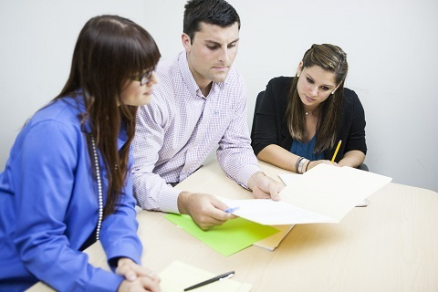 Three people leaning on a table and examining some documents. The man here is in between the two ladies.