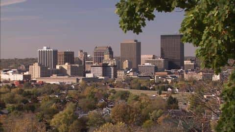 The skyline of Dayton with six outstandingly tall towers and a cluster of smaller houses shielded by a vegetation of trees