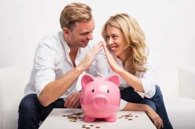 A couple smiling and putting their hands together, with a piggy bank on a white table in front of them.