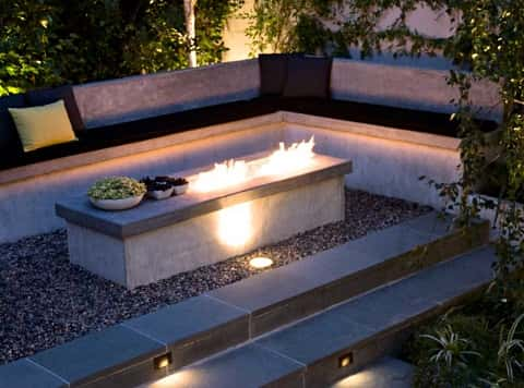 Two stairs lead up to a lighted rectangular firepit in the shape of a tomb surrounded by a padded concrete seat.