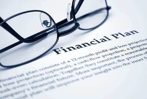 "Close up picture of a financial plan with the heading ""financial plan"" clearly visible, and glass above it."