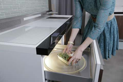 A woman putting a bowl of vegetables in the top compartment of a refrigerator.