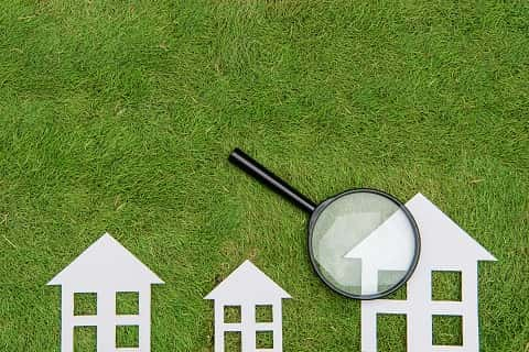 Three different sizes of plain figures of houses lying on a green grass with a magnifying glass on the biggest.