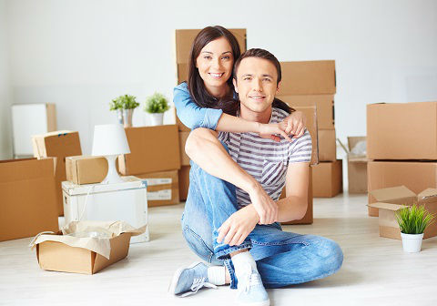 Young male sitting on the floor of a new home and a young female sitting behind him with her hands around his neck. Brown boxes are behind them.