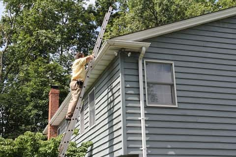 Man on top of a ladder looking at the gutter of a grey painted wooden building.