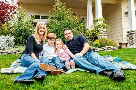 A couple and their two kids snuggled between them sitting down together on their lawn.