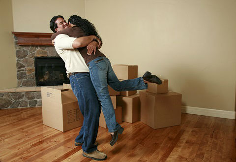 A young couple hugging inside of a unfurnished room. Several boxes lie on the floor waiting to be opened.
