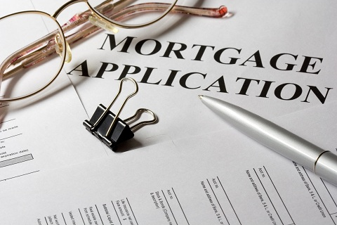 A close-up picture of a document for a mortgage application with a pen, a pair of specs and a document paper clip.