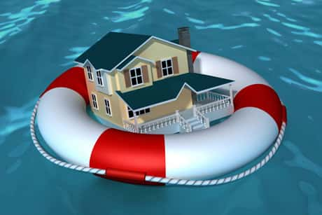 Representation of insurance, with a house in a red and white lifesaver tire in a swimming pool.