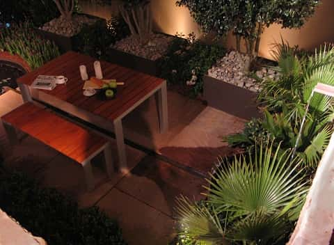 Brown wooden table and bench in the middle of an artificial garden ideal for relaxation.