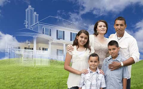A latino family standing on the lawn. In the background is the skeletal representation of a house.