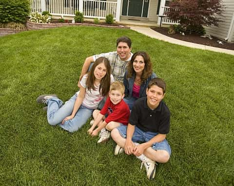 Family happily sitting on the lawn outside of their home. There is a couple with three children smiling into the camera.