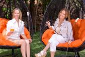Two ladies, Lori and Kellie, sitting on elegant orange and black outdoor furniture, and sipping drinks.