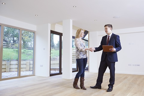 Man on suit holding a brown file on his left hand and shaking a young lady & What to Expect at Your New Homes Final Inspection