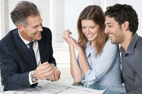 A young couple examining floor plans and smiling, while an agent extends a key to them.