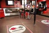Bar with seats designed in the shape of car tires. The logo of the car company is on the floor and wall.