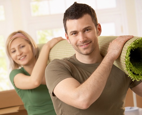 Young man and woman carrying a green rolled up rug on their shoulder are smiling.