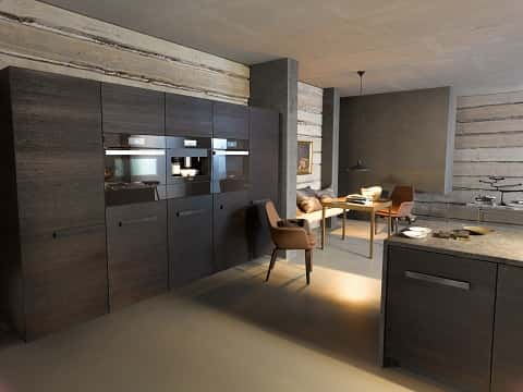 A modern kitchen showing a series of well-designed and furnished grayish-brown ovens manufactured by Miele Company.