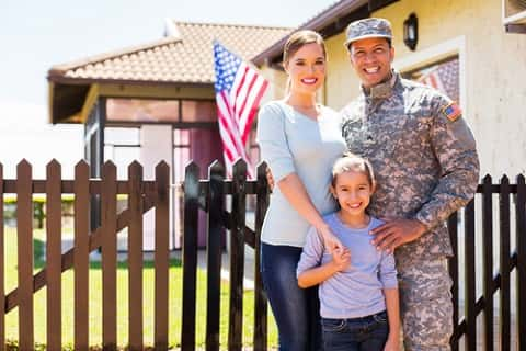 A photo family of one U.S. military in front of the fence of their home. In the background, the U.S.A. flag is flying.