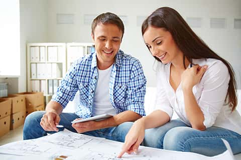 A young couple examining floor plans and smiling. In the background is the whitewashed interior of their house, and there are some packing boxes to the left-hand side.