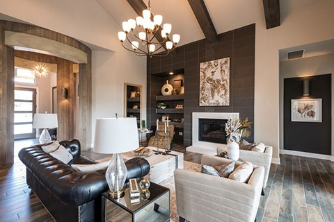 A neatly finished and furnished living room using wooden brown, cream and a touch of black.