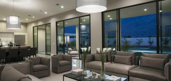 An example of a room with glass doors and beautifully decorated with grey and white and overlooking a swimming pool outside