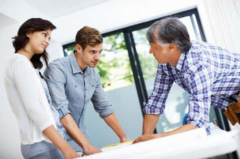 Couple examining floor plans along with a middle-aged builder. The three of them are presently engaged in a discussion.