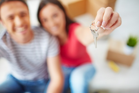 Couple happy after getting their new home. The couple holds up their key and it is superimposed on the picture.