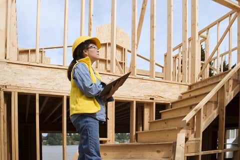 A female construction worker in yellow attire holding a document and looking up a wooden staircase.