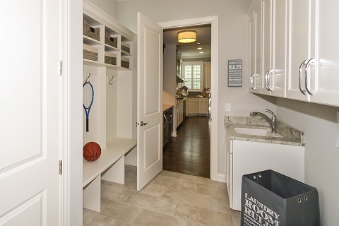 A laundry room and an opened door that permit to observe part of the kitchen. A baseball ball and a tennis racket are in the laundry room.