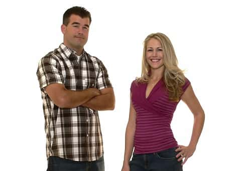 A couple smiling at the camera as they appear on a white background.
